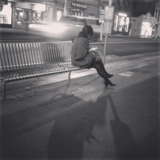 Day 19 - Woman sits hunched in the cold evening air waiting for a tram. She is alone.