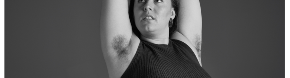 Black and white photo on a woman from waist up. She wears a ribbed sleeveless top. Her arms are raised above her head clearly showing underarm hair.