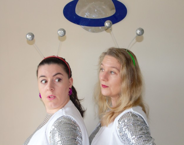 Head and shoulders view of two women in profile wearing novelty headbands. One looks surprised. They both wear silver costumes.