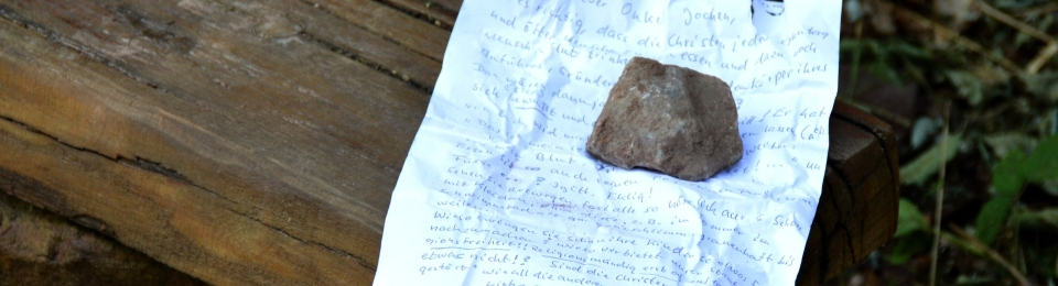 A rock sits on a piece of crumpled paper. Writing on the paper is illegible. The paper is on a wooden sleeper bench seat.