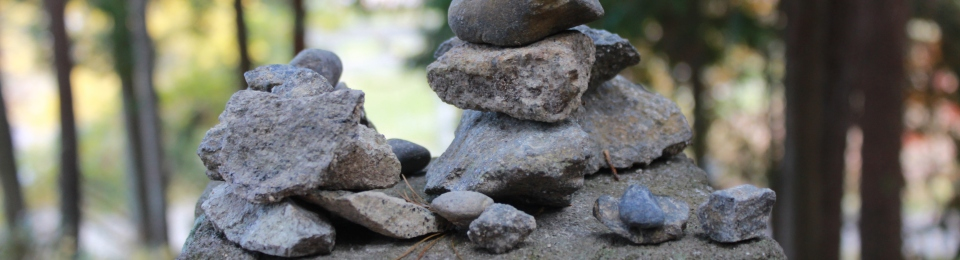Close up of a collection of small rocks arranged on top of a stone post.