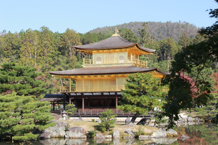 large three tiered Japanese pagoda style building. upper two floors are covered in cold. Forest and mountain in background.