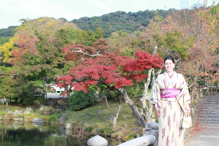 A white woman wearing traditional Japanese kimono stands in front of a lake, tree with striking red foliage, and a mountain in the background. Kyoto, Japan.