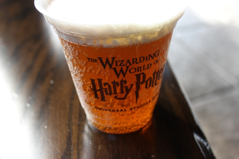 Close up of cup containing frothy yellow soft drink. Text on cup reads 'The Wizarding World of Harry Potter Universal Studios Osaka'