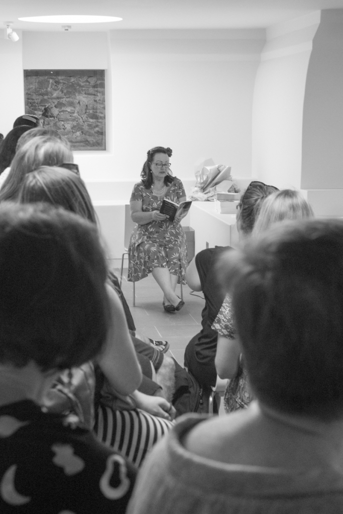 Black and white. An older woman with black hair sits reading from a book to a group of people.