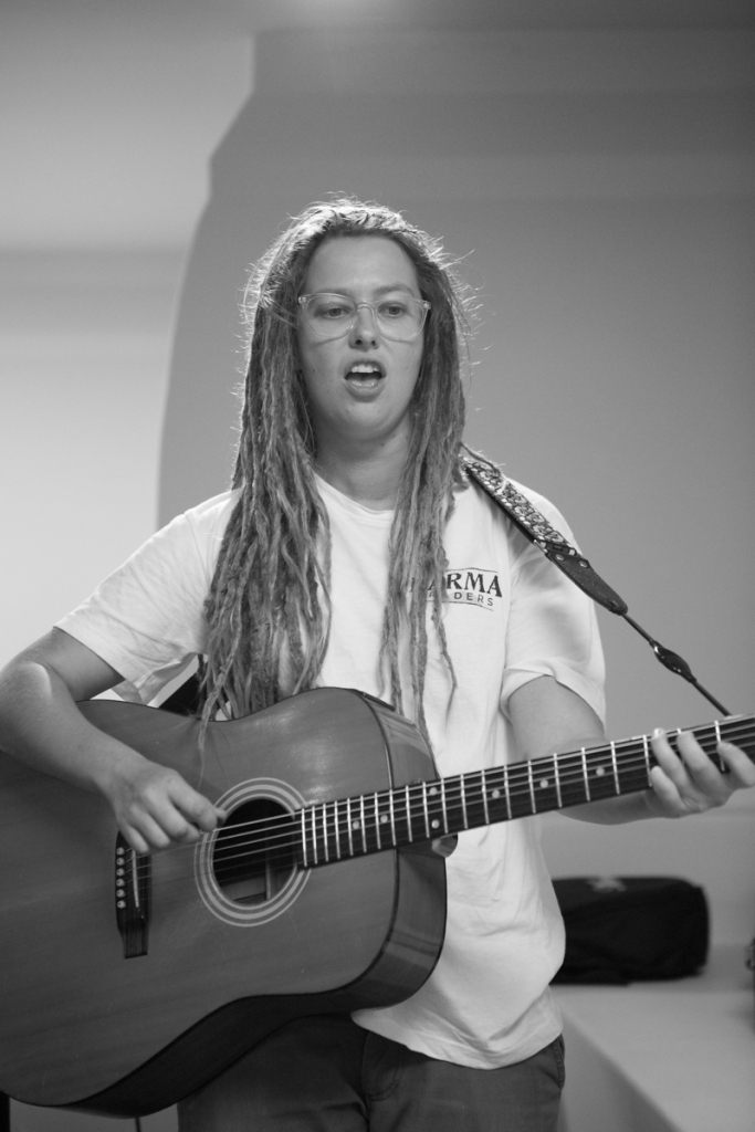Black and white. A woman with long blond dreadloacks, wearing a white t-shirt plays the guitar and sings.