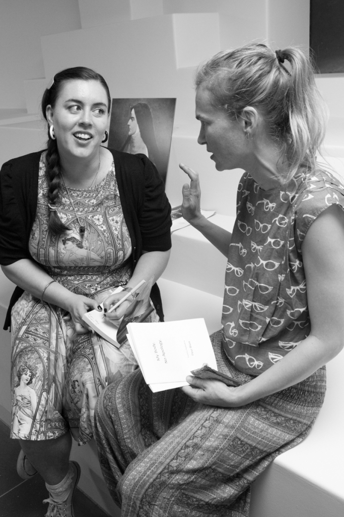 Black and white. A woman with long brown hair signs a book for a woman with blond hair. They are seated.