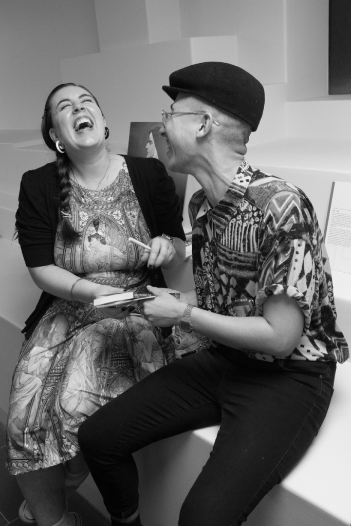 Black and white. A woman with long brown hair throws her head back laughing. A non-binary person next to her is also laughing. They are seated and the woman hands her companion a book.