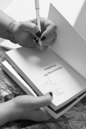 Black and white photo of a woman signing a copy of her book. Close up of hands and book only.