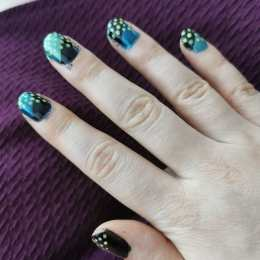 A right hand displaying black, teal and yellow patterened nail polish