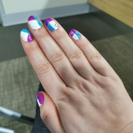 A right hand displaying blue, pink and white patterned nail polish.