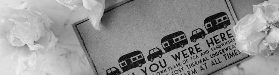 Stock image in black and white. A card showing stylised cars pulling caravans, text reads 'Wish you were here'. Also features heads of flowers around the card.