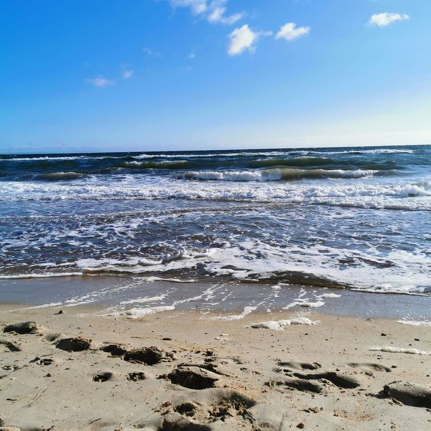 photo of sand and shallow waves on a sunny day in late evening with blue skies.