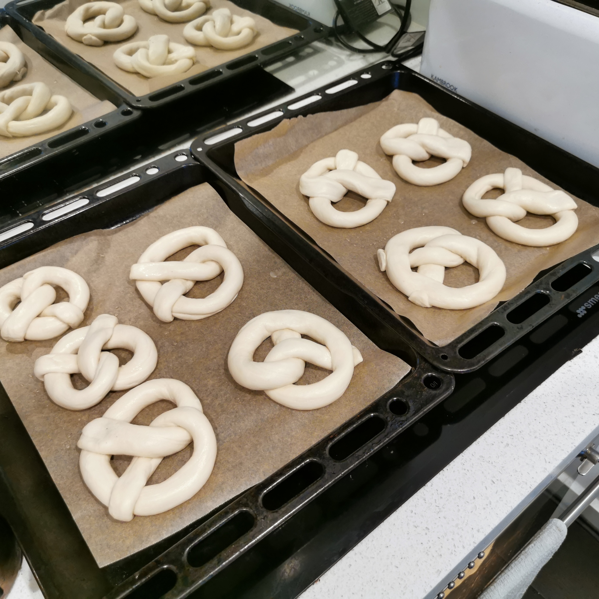 9 unbaked soft pretzels sit in baking trays on top of the stove
