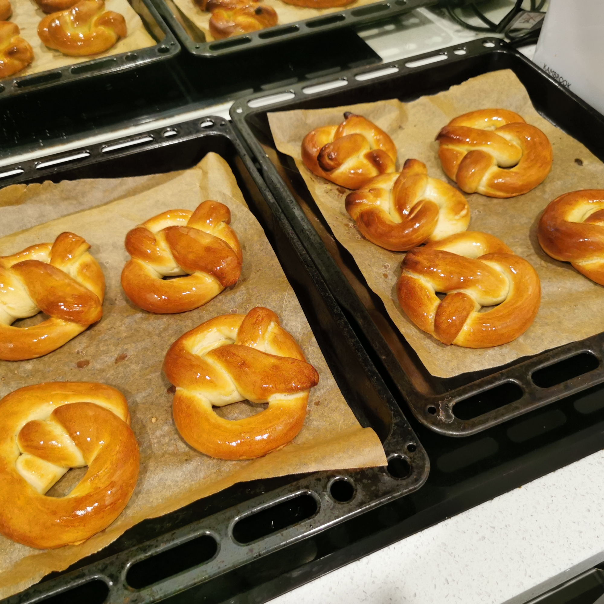 9 Freshly baked soft pretzels sit on baking trays on top of the stove