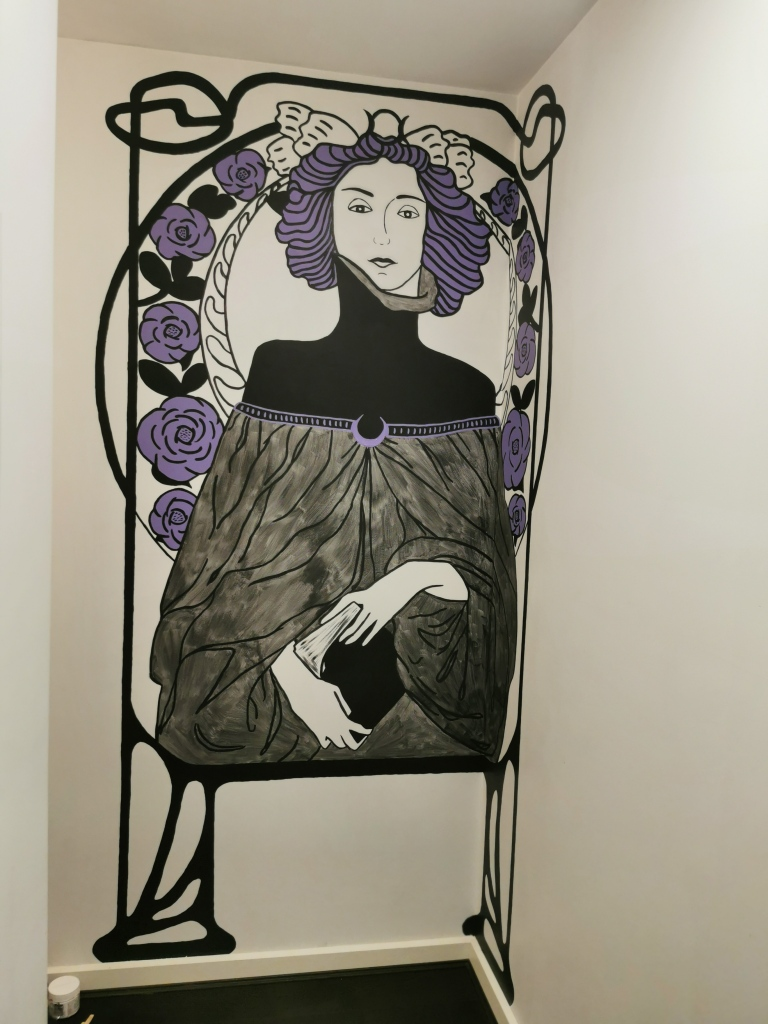 A black, white and purple stylised mural of a woman holding a book. she is surrounded by art nouveau border designs.