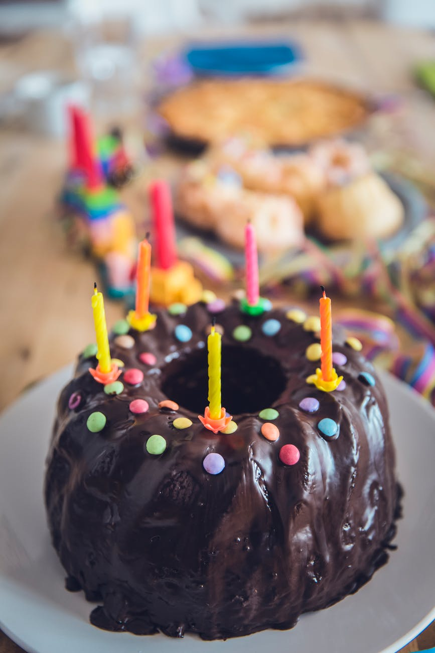 Chocolate bundt cake with coloured smarties and candles on top.